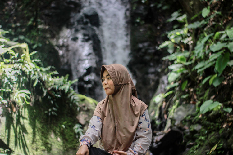 Woman sitting against waterfall