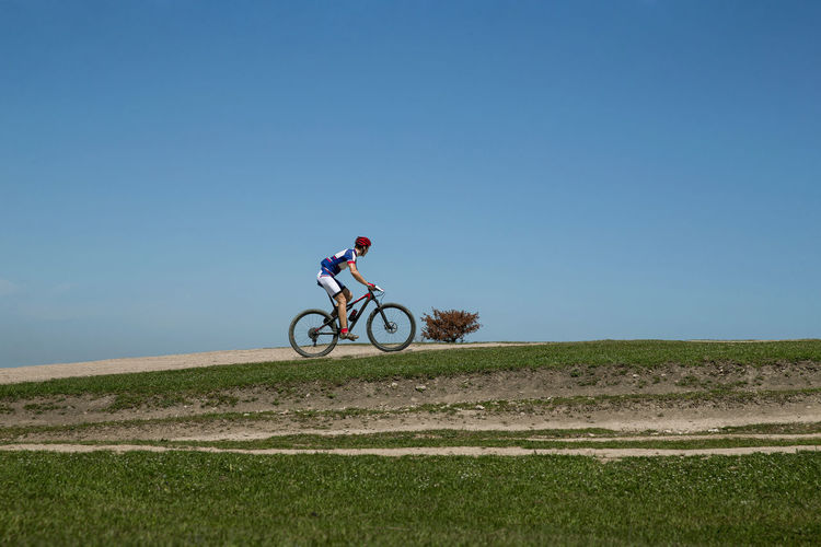 Man riding bicycle on field against clear sky