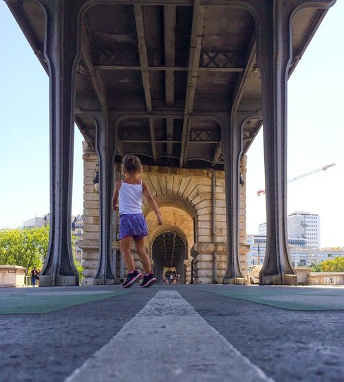 Low angle view of girl jumping under bridge