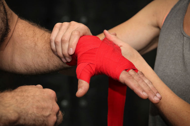 Midsection of man applying wristband on hand of boxer
