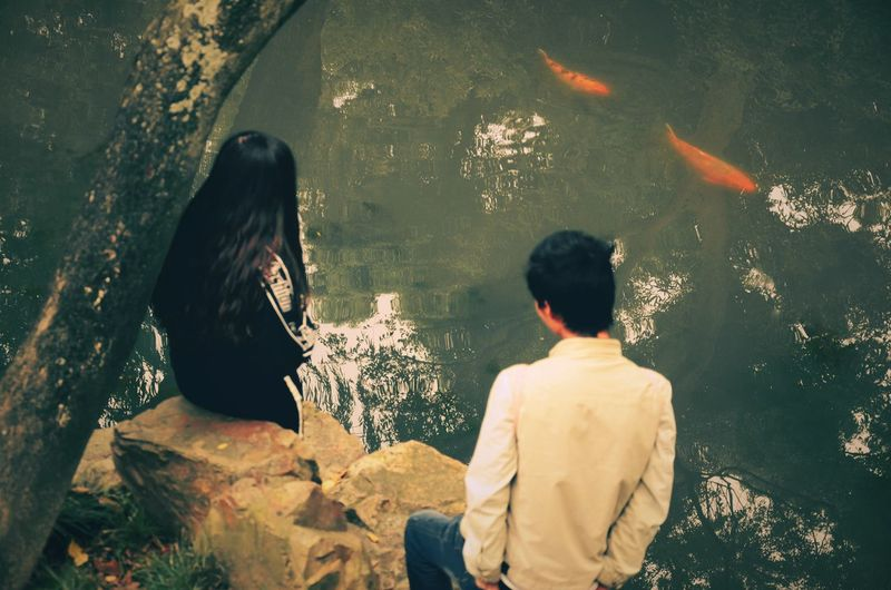 The boy is trying to talk to the girl, like the fish in pursuit of the other one, i guess.😃 Rear View Adult Two People Women Day Togetherness Water Adults Only Sitting People Outdoors Cityscape Only Men Real People Men River Fish Street Photography