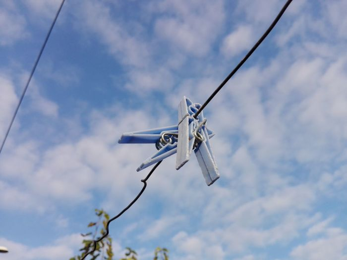 Low angle view of clothespins hanging from clothesline against sky