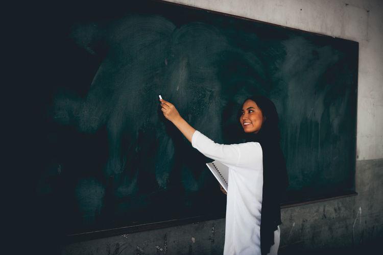 Side View Of Teacher Writing On Blackboard In Classroom