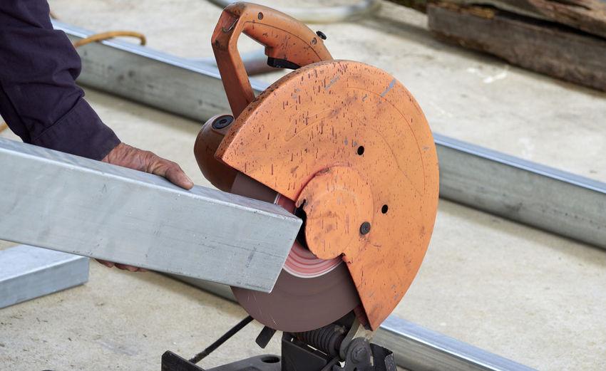 Cropped hand of man using grinder in workshop