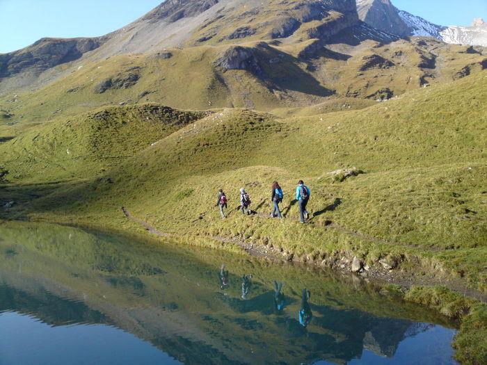 Rear vie of people walking by lake on mountain