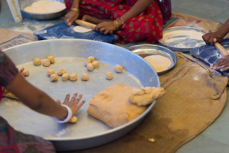 Women making Indian flat bread, called chapati, on a big silver plate. Day Flatbread  Food Food And Drink Freshness Human Body Part Human Hand Indoors  Lifestyles Making Plate Preparation  Preparing Food Real People Table