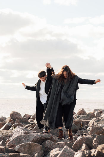Lesbian women holding hands while walking on rock against sea and sky