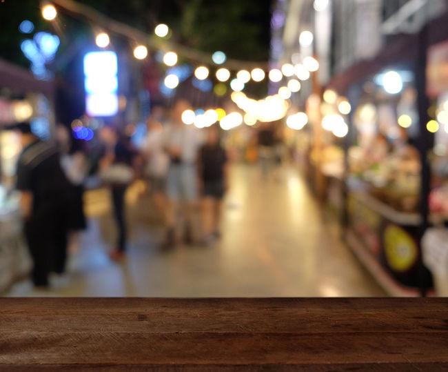 Defocused image of people walking on illuminated road at night