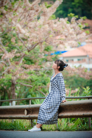 Side view of woman sitting on railing against trees