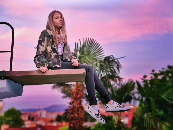 Full length of woman sitting against sky during sunset