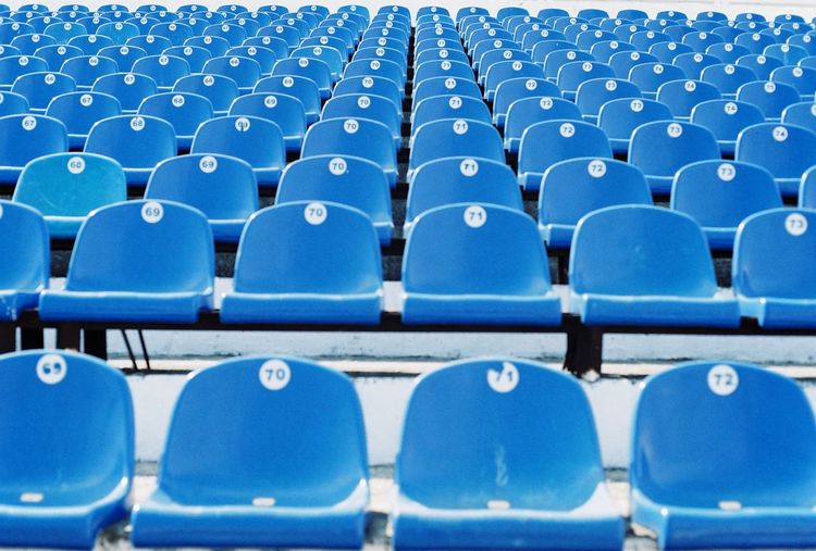 Low Angle View Of Blue Plastic Seats In Stadium