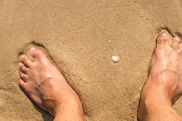 Low section of man legs on sand