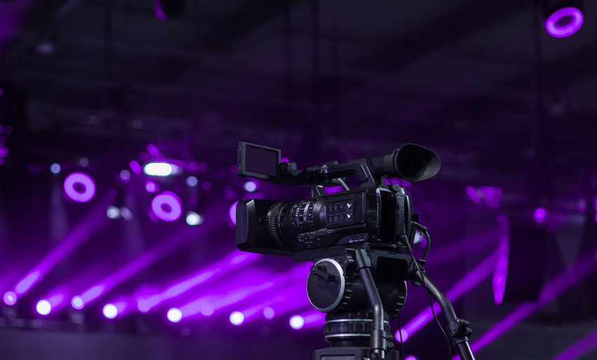 Low angle view of television camera against illuminated spot lights
