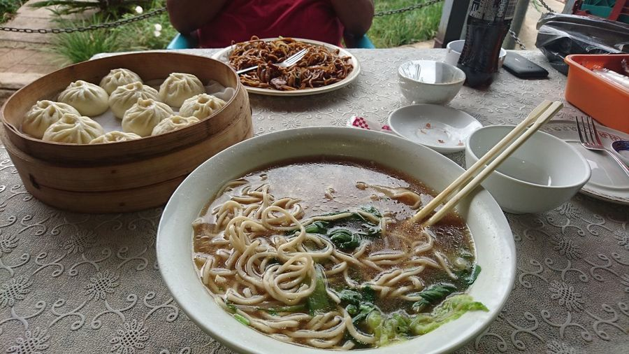 High Angle View Of Noodle Soup With Chinese Dumplings Served On Table