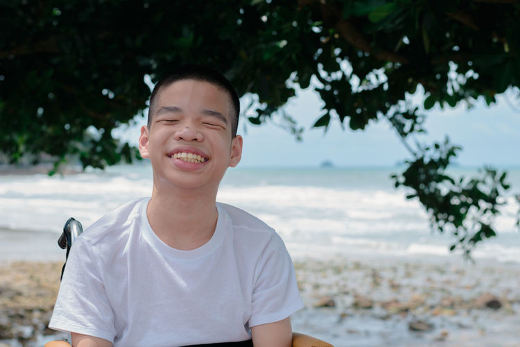 Close-up of smiling boy sitting on wheelchair against sea
