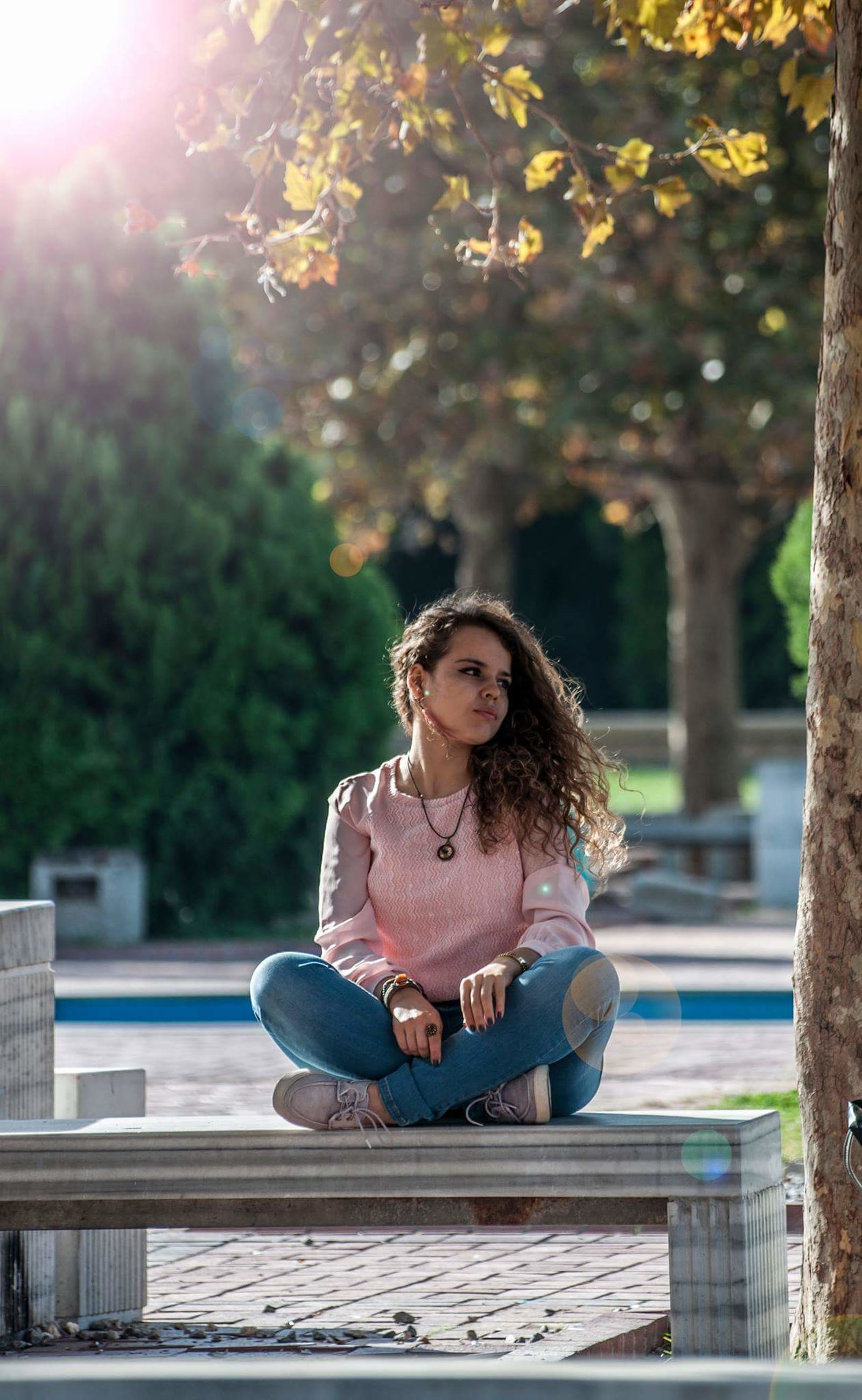 one person, sitting, young women, casual clothing, young adult, outdoors, tree, leisure activity, front view, sunlight, park - man made space, day, full length, women, relaxation, real people, beautiful woman, lifestyles, medium-length hair, student, nature, adult, people