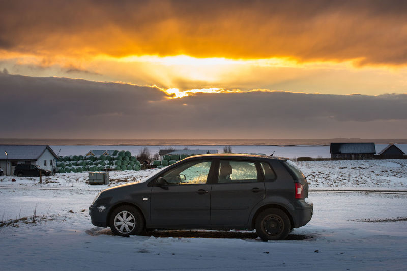 Car on snow covered landscape against sky during sunset