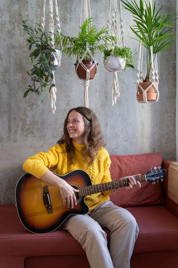 Smiling woman playing guitar on sofa