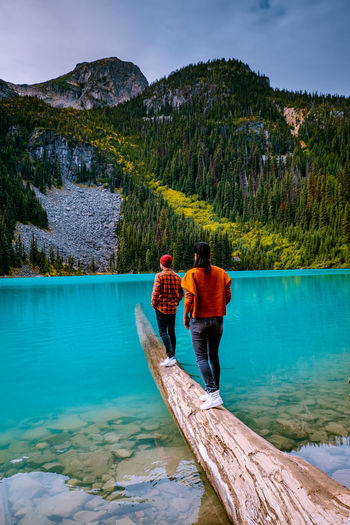 Rear view of couple standing on wood in lake against mountains and sky
