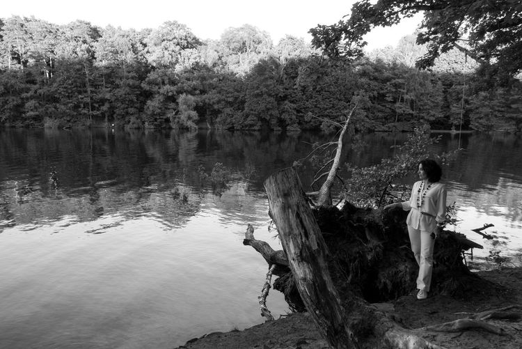 Full length of woman standing by lake at forest