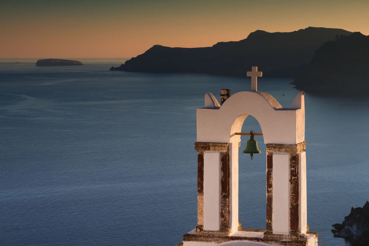 Bell tower against sea during sunset