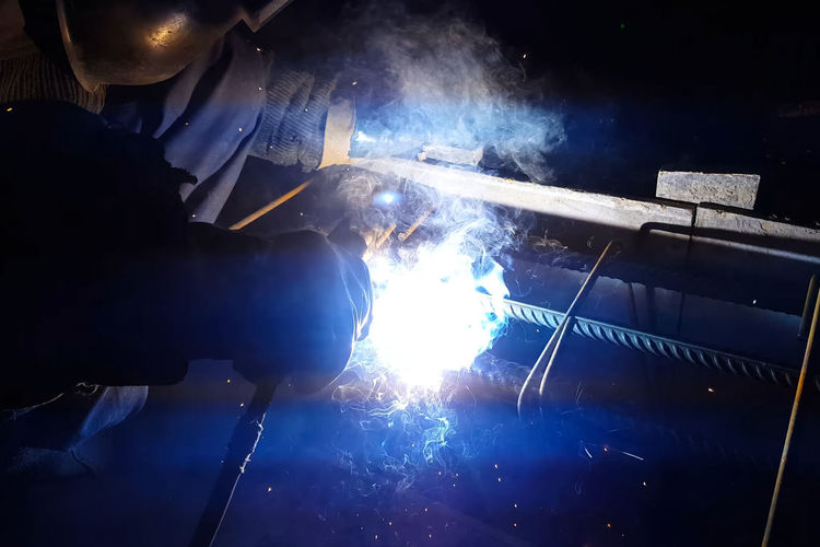 Occupation Heat - Temperature Welding Metal Industry Real People Indoors  Working Burning Skill  Industry Blurred Motion Smoke - Physical Structure Men Fire - Natural Phenomenon One Person Holding Protective Workwear Protection Workshop Sparks Hand