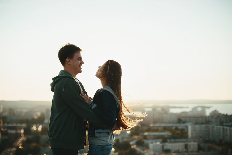 Couple embracing while standing against sky