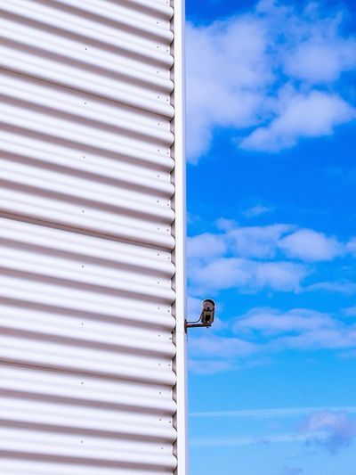 Close-up of surveillance camera on roof against blue sky