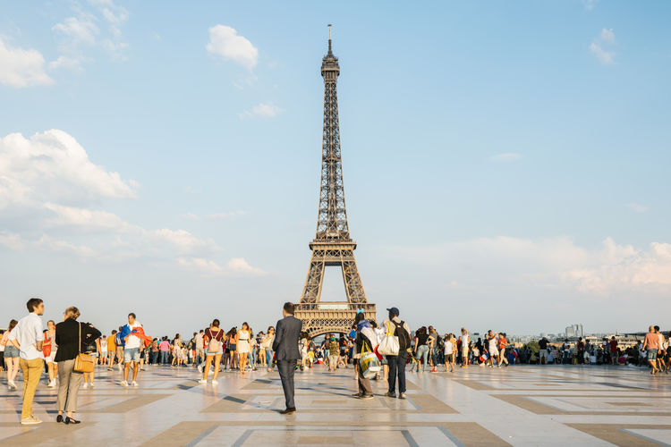People Standing By Eiffel Tower In City Against Sky