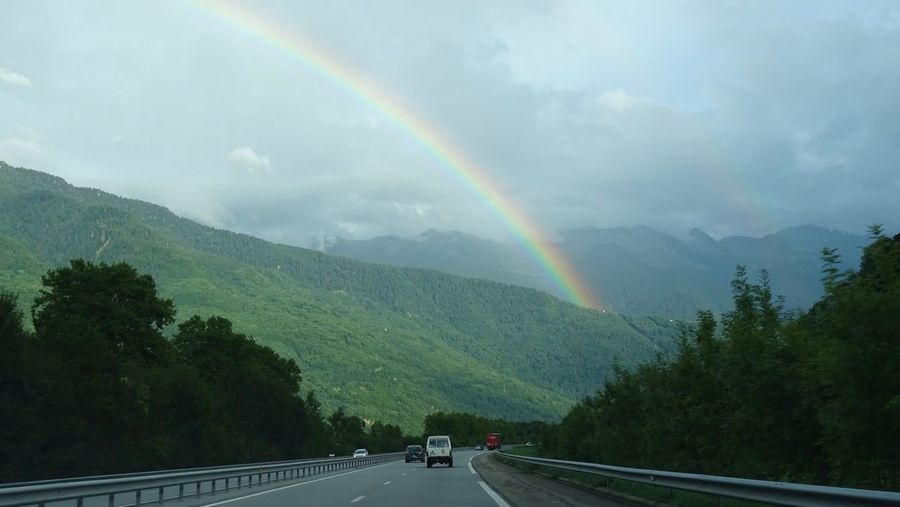 Scenic view of rainbow over mountain against sky
