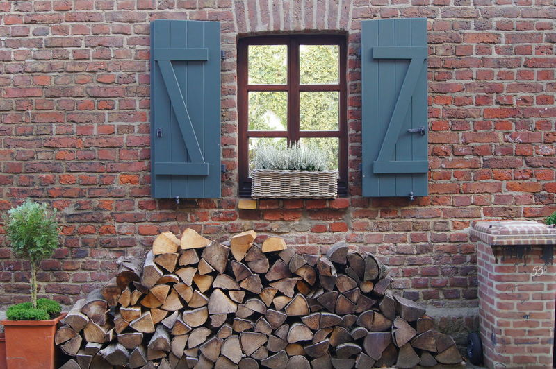 Firewood Stack In Back Yard Against Brick Wall House