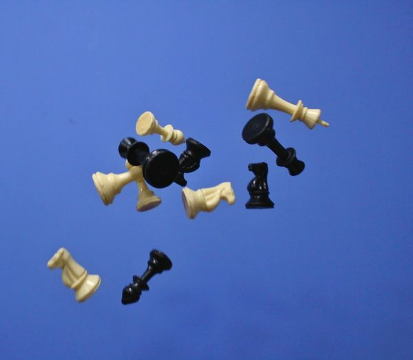 Low angle view of chess pieces against clear blue sky