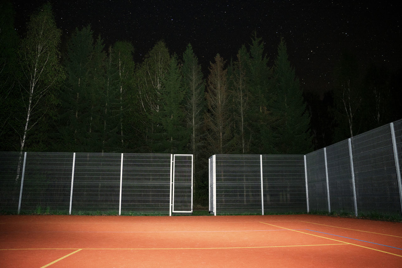 View of empty court against trees at night