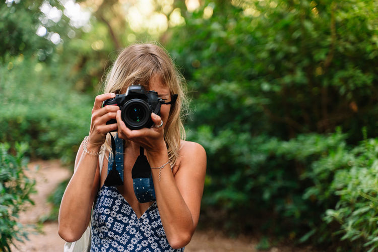 Midsection of woman photographing against plants