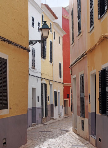 a beautiful sunlit narrow cobbled quiet street of old houses painted typical bright colors in ciutadella menorca spain Street Minorca Narrow Cobblestone Tourism Built Structure Architecture Building Building Exterior Window Residential District City No People Day Direction Outdoors Town House The Way Forward Nature Door Entrance Alley Apartment