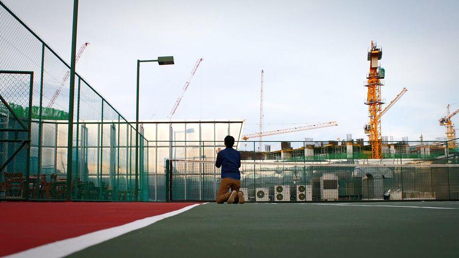 Rear View Of Man Kneeling While Praying At Tennis Court