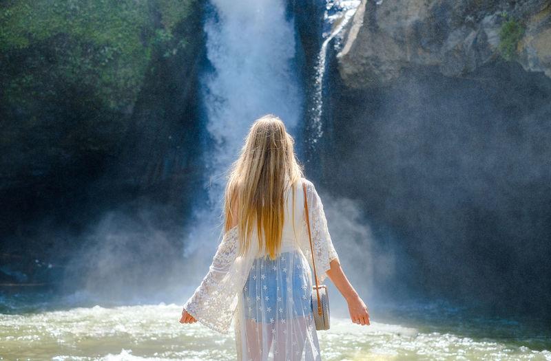 Girl on the background of a waterfall. tegenungan, bali, indonesia.