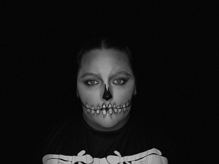 Portrait of young woman with spooky make-up against black background