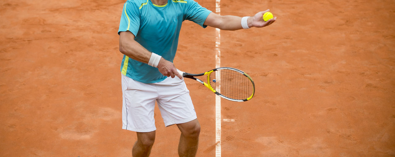 Midsection of man playing tennis