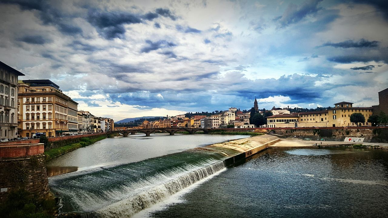 Arno River Amidst Buildings Against Cloudy Sky