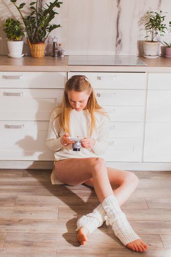 Full length of girl sitting on wooden floor at home