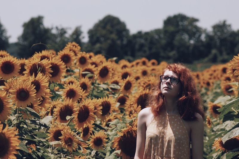 Look up Young Adult Young Women Redhead Flower One Person Nature Beauty In Nature Beautiful Woman Beauty Focus On Foreground Real People Plant Lifestyles Outdoors Standing Tree One Young Woman Only Women Portrait Freshness EyeEm Selects Sunflower