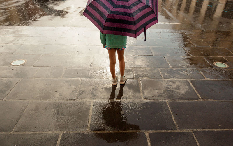 Low section of child under an umbrella