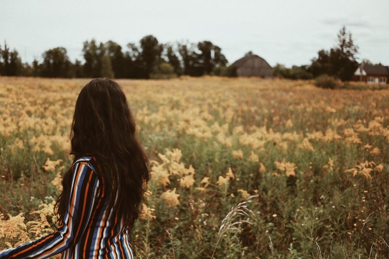 Rear view of young woman standing on flowering field