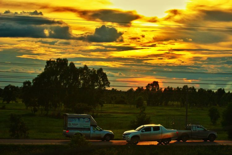 Cars on field against sky during sunset