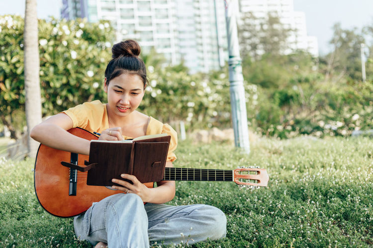 Smiling woman making note while sitting with guitar at park