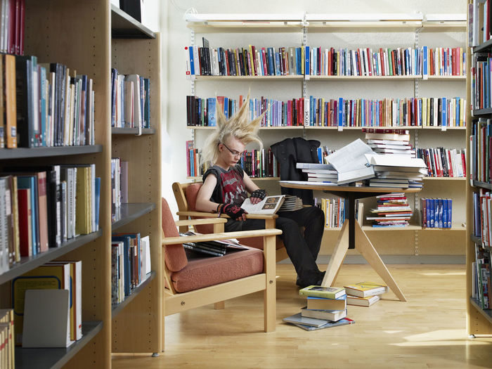 Women sitting on table in library