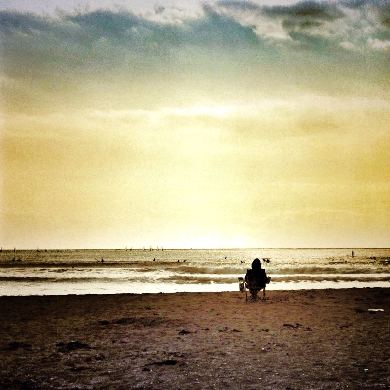 Lone person sitting on beach overlooking sea