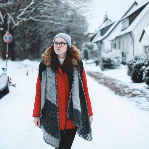 Woman Walking On Snow Covered Road In City