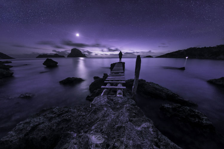 Woman Standing On Pier Over Sea At Night